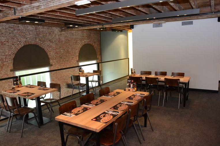 Op een halfopen tussenverdieping staan ook nog een aantal tafeltjes.