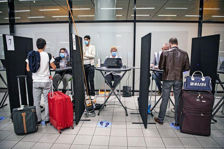 De GGD op Schiphol controleert reizigers uit Zuid-Europa op vrijwillige basis op het covid-19-virus. Beeld Guus Dubbelman / de Volkskrant