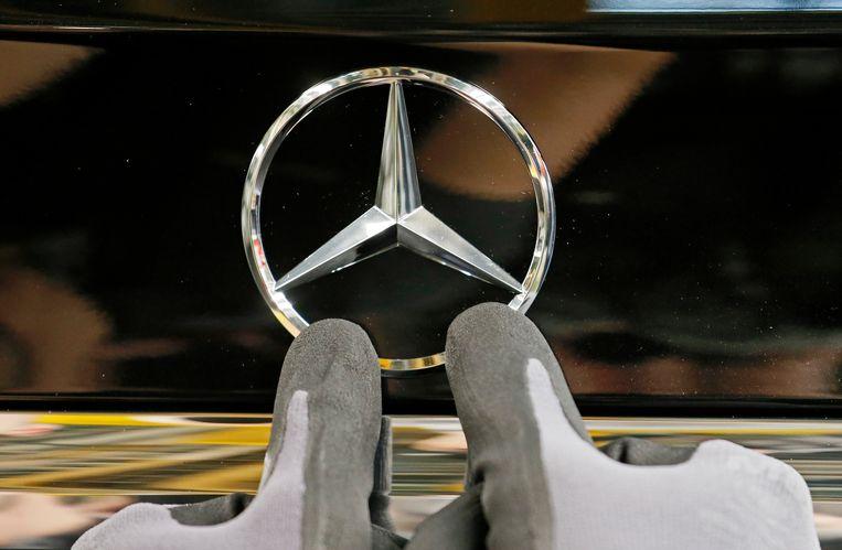 Een Mercedes-ster wordt door een arbeider op een auto geplaatst.