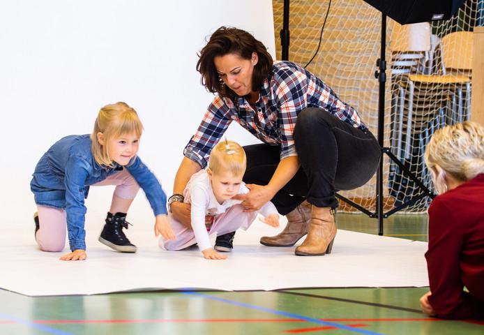 De fotograaf (rechts) is met hulpmoeder Corina bezig om Eline en Marit op de foto te zetten in de gymzaal van de openbare basisschool Het Anker in Heinenoord. Op het inzetje de 6-jarige Tobias en zijn broertje Fabian (2).