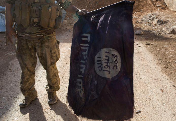 Soldaat van de Syrische Democratische Strijdkrachten met een vlag van IS in Raqqa.
