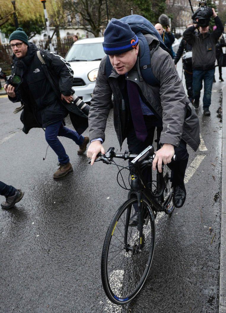De burgemeester fietst weg nadat hij journalisten te woord heeft gestaan. Beeld afp