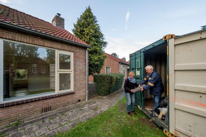 Wijnand Storm neemt wat rommel van een buurvrouw aan bij de container. Op de achtergrond de seniorenwoningen die plat gaan.