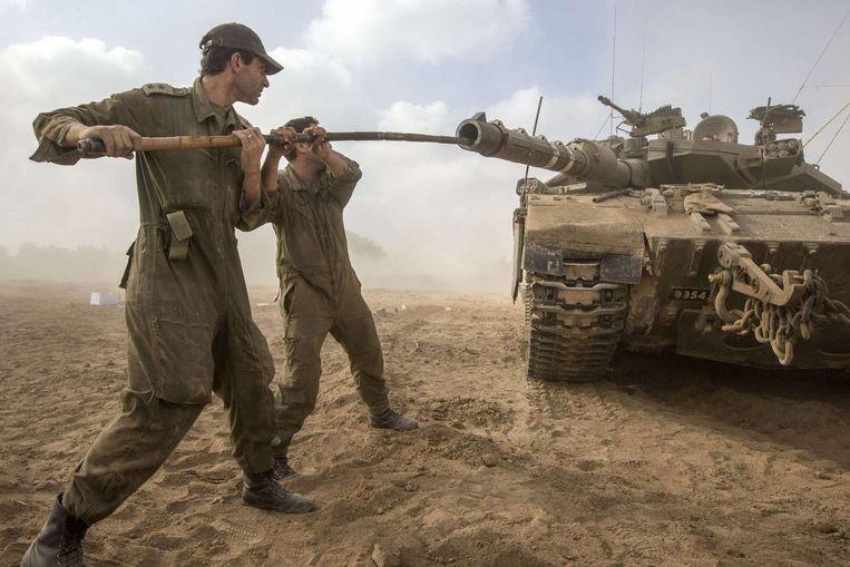 Israëlische soldaten maken de loop van hun tank schoon op de grens tussen Israël en de Gazastrook. Beeld afp