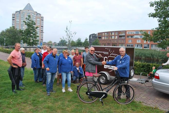 Leden van Sub70 overhandigen de fiets aan een vertegenwoordiger van het KWF.