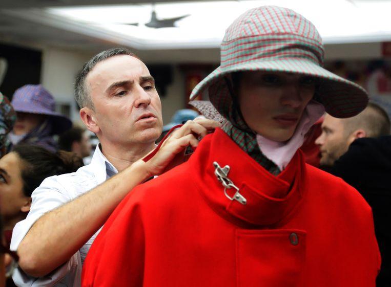 Modeontwerper Raf Simons doet een paar laatste aanpassingen voor zijn show tijdens Fashion Week in New York. Beeld AP