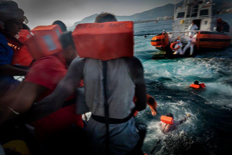 Voor de kust van Sicilië springen migranten vanaf een reddingsschip van ngo Open Arms in het water, zodat de Italiaanse reddingsbrigade ze wel aan boord moet nemen. Het schip van Open Arms werd zowel door de Maltese als Siciliaanse autoriteiten toegang tot de haven geweigerd. Beeld AP