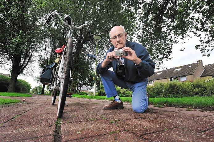 Jacques Vermeulen (80) maakt een foto van een gevaarlijke scheur in het fietspad op de Flaneerdijk.