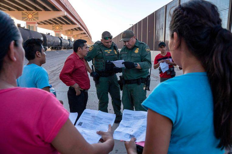 Amerikaanse grenswachters controleren de documenten van migranten die de Rio Grande oversteken van Juarez, Mexico naar El Paso, Texas.