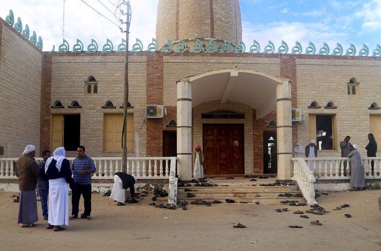 Overlevenden staan een dag later bij de  Al Rawdah moskee.