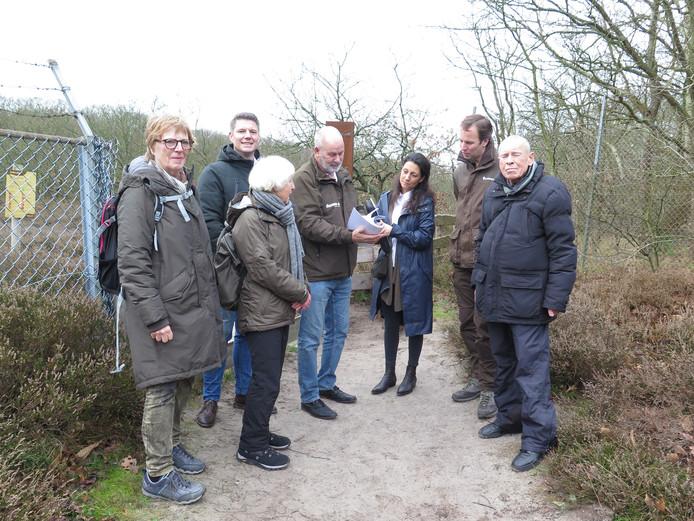 Een groep wandelaars biedt de petitie aan Dunea en Het Zuid-Hollands Landschap aan.