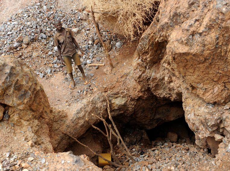 Een jongen staat bij de ingang van een illegale goudmijn in Burkina Faso. Archiefbeeld.