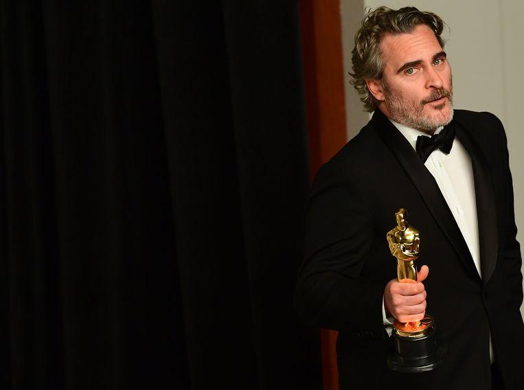 Acteur Joaquin Phoenix poseert met zijn Oscar voor beste acteur voor zijn rol in de film Joker. Beeld AFP