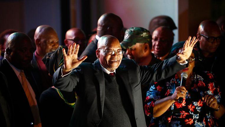 Zuma, omringd door ANC-getrouwen, spreekt dinsdagavond aanhangers voor het parlementsgebouw in Kaapstad toe, na een motie van wantrouwen te hebben overleefd. Beeld Nic Bothma / EPA