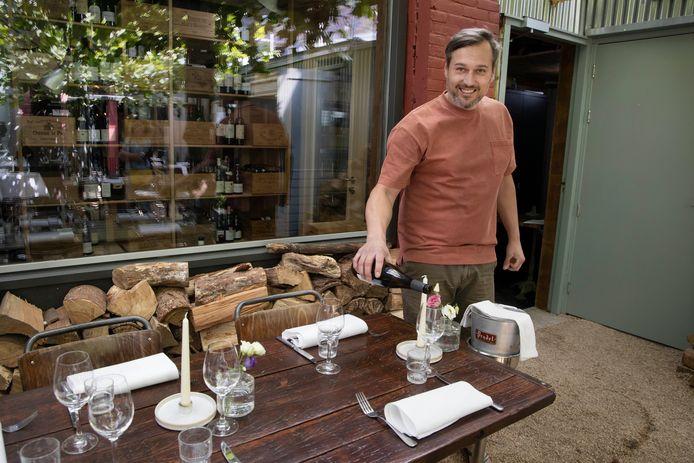 Elroy Slijkhuis in de overkapte tuin van zijn restaurant Flores. Achter hem de twee geklimatiseerde wijnkasten die de koks bouwden. Mocht er een lockdown komen, dan heeft Elroy Slijkhuis een Plan B.