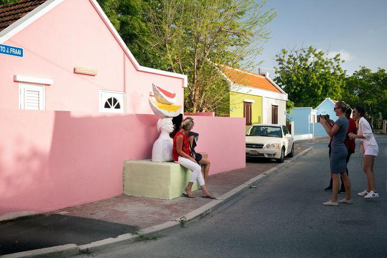 Bewoners poseren bij het werk van kunstenaar Carlos Blaaker in Otrobanda. Beeld Els Zweerink