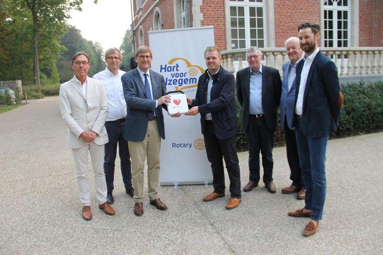 De bestuursleden van Rotary overhandigen alvast symbolisch een eerste defibrillator aan burgemeester Bert Maertens.