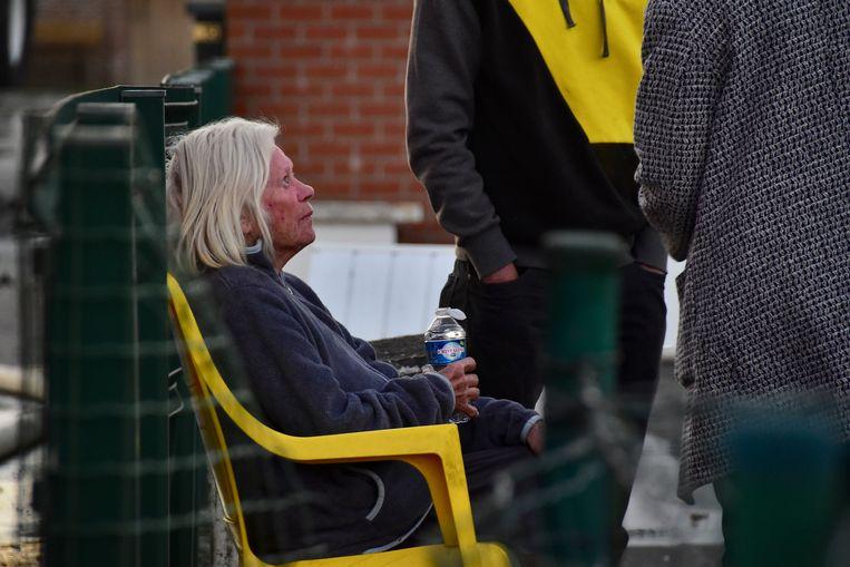 Bewoonster Christiane Vanrobaeys moest bekomen in een tuinstoel, met een flesje water in de hand.