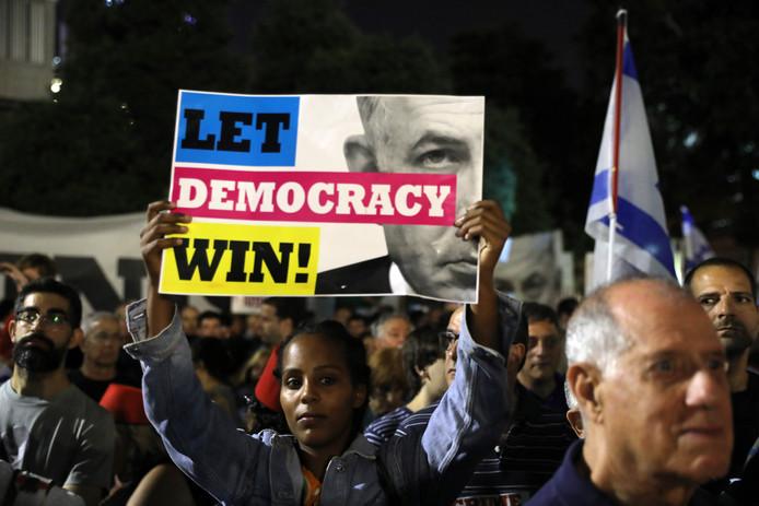 'Laat democratie winnen', staat er op het bord dat een van de demonstranten omhoog hield.