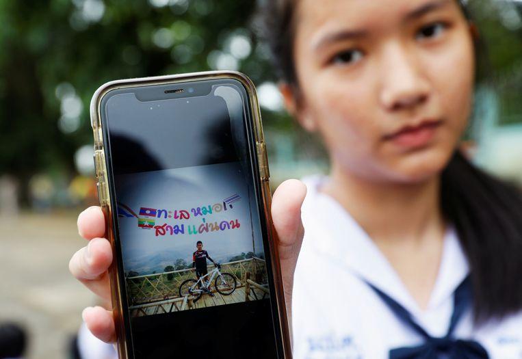 Een klasgenote van  Prachak Sutham (13), een van de vermiste voetballers, toont een foto van hem op haar smartphone. Heel Thailand leeft erg mee met het nieuws.