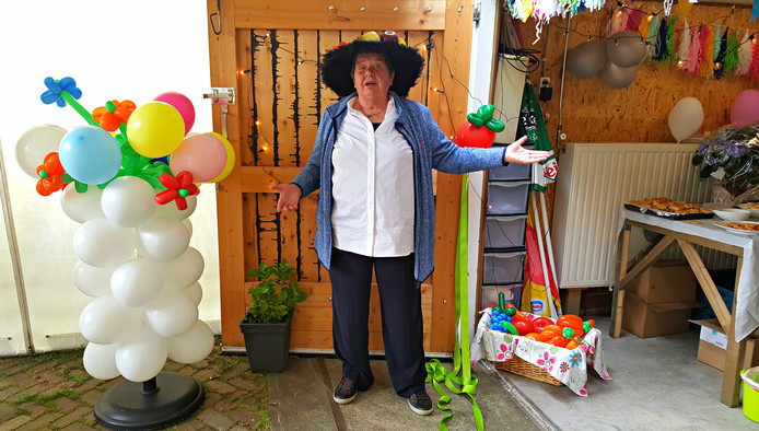 Corry Quist was goed gemutst tijdens de opening van haar verswinkel. Ze droeg een bijpassende hoed vol fruitwaren.