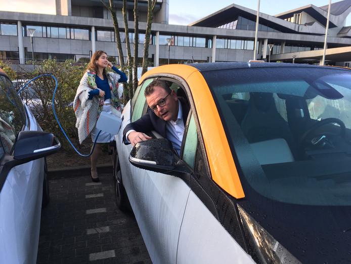 Annemarie Spierings steekt de stekker in de elektrische auto, collega-gedeputeerde Renze Bergsma steekt zijn hoofd uit het raam.