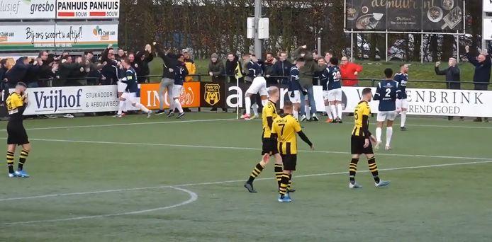 Supporters van Sparta Nijkerk betreden het veld om de winnende goal in blessuretijd tegen DVS'33 te vieren.