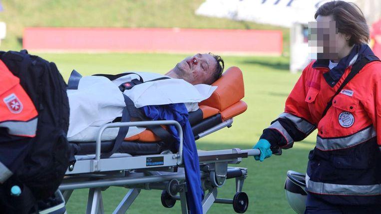 Christian Müller wordt met bloedend aangezicht afgevoerd.