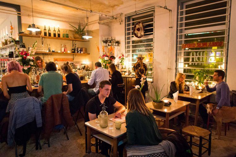 Gasten zitten aan formica tafeltjes, op lage krukjes, of aan de bar, en eten met hun handen Beeld Mats van Soolingen