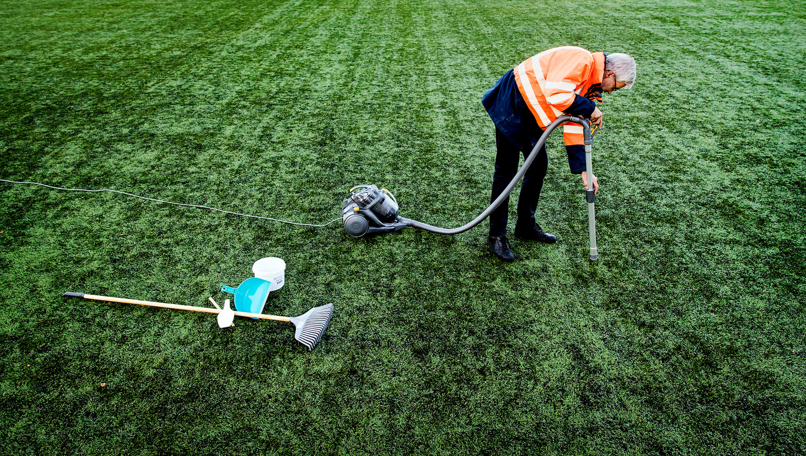 Een medewerker van Vereniging Band en Milieu verzamelt rubberkorrels op een voetbalveld van kunstgras van voetbalvereniging Roda 23.