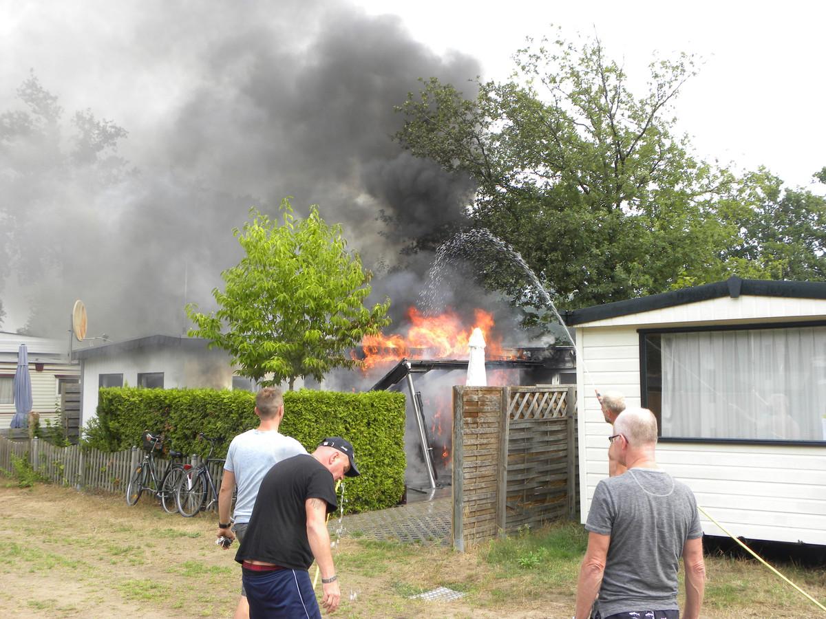 Campinggasten proberen de brand te blussen.