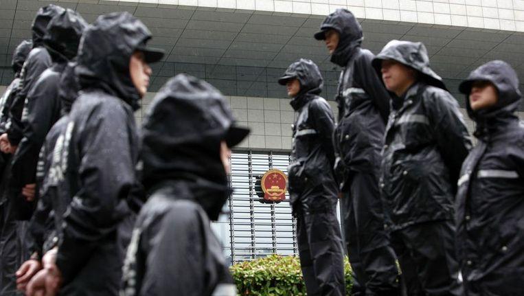 Politie-agenten buiten de rechtbank waar het proces tegen Kailai plaatsvond. Beeld reuters