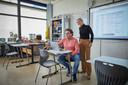 Directeur Petra van Dam en leraar Ton Rekelhof tijdens de Duitse les. De kinderen zitten thuis achter de laptop.