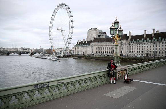 Deze doedelzakspeler houdt de moed erin aan een lege Westminster Bridge in Londen.