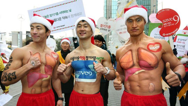 Zuid-Koreaans acteur en sportinstructeur Arnold Hong (rechts) en twee anderen tijdens een campagne van de Korean Organ Donor Program in Seoel. Zuid-Korea, op 18 december 2015. Beeld anp