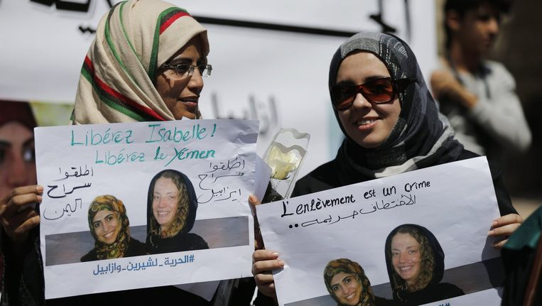 Vrouwen houden posters vast met foto's van Isabelle Prime en haar tolk Shereen Makawi in Sanaa. Beeld reuters