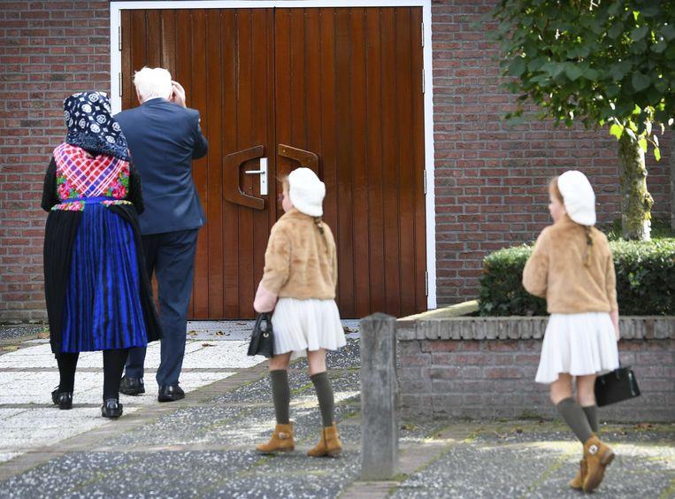 In het diepgelovige dorp Staphorst komen kerkgangers aan bij de Hersteld Hervormde Kerk. Beeld ANP