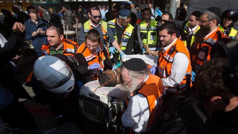 Israelische hulpverleners dragen een gewonde Palestijn weg. De man werd neergeschoten nadat hij twee bewakers aanviel.