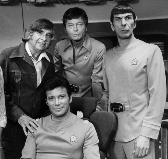 Bedenker van de SF-serie, Gene Roddenberry. Naast hem leden van de cast: William Shatner, DeForest Kelley en Leonard Nimoy, alle drie in Star Trek-plunje, mét het bekende logo als insigne.