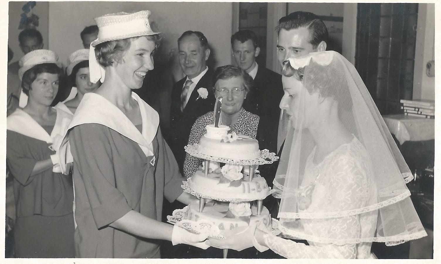 Een hostess overhandigt namens de organisatie een bruidstaart aan de winnaars van de verkiezing Ad en Thea Tabbers.