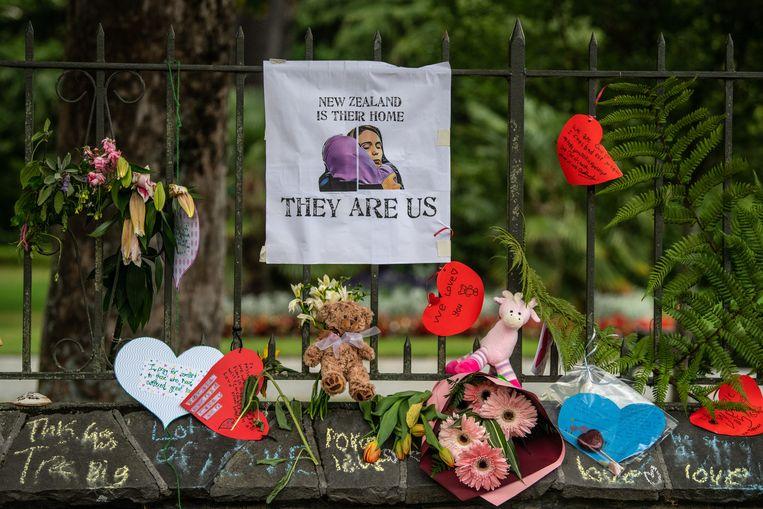 Bloemen, briefjes en knuffels bij een hek in de botanische tuin in Christchurch. Beeld Getty Images