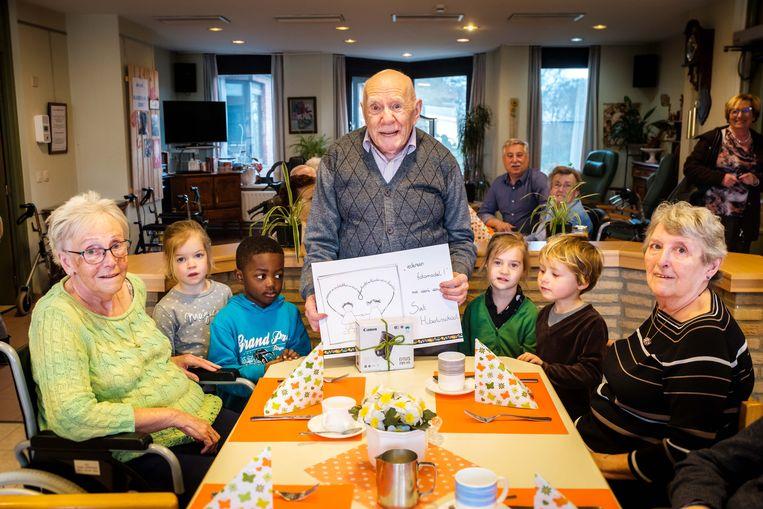 De kinderen van de Sint-Hubertusschool schenken een fototoestel aan de bewoners van Maria Boodschap.