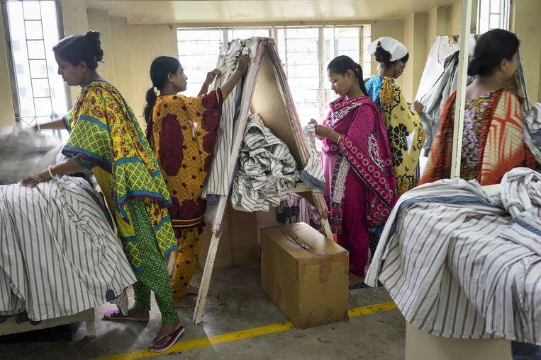 Arbeidsters knippen draadjes af van kledingstukken in het atelier van MGL, Dhaka. De kleding wordt onder meer verkocht aan H&M. Beeld Catrien Ariens