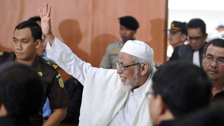 Bashir zwaait naar zijn aanhangers nadat hij tot 15 jaar werd veroordeeld. © ANP Beeld null