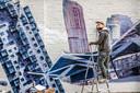 Gevelkunstenaar Paul Watty bij zijn project aan de Hoogvensestraat.