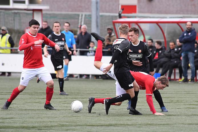 Beeld uit de thuiswedstrijd van JVC Cuijk tegen Jong FC Volendam. Lars Loermans gaat onderuit tegen twee tegenstanders, links Furkan Alakmak