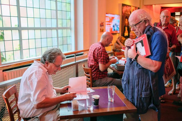 Cartoonist Kees Willemen (links) tijdens een signeersessie.