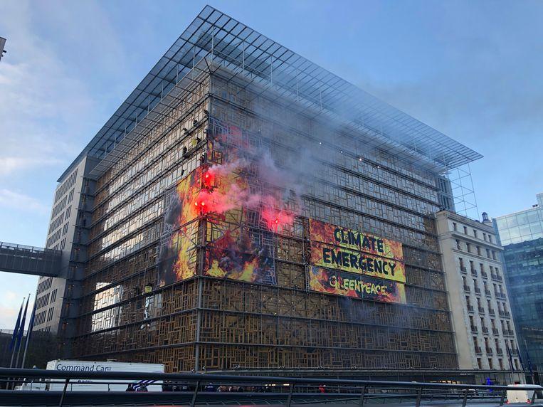 Spandoeken van Greenpeace en fakkels bij het Europa-gebouw in Brussel. Beeld BELGA