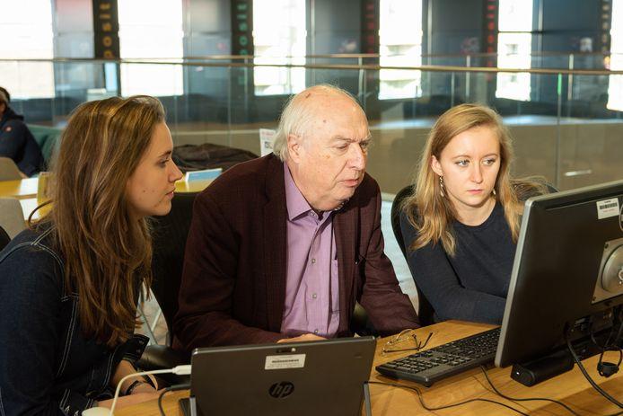Ad van Liempt speurt, omringd door twee studenten geschiedenis van de Universiteit Utrecht, in de beeldbank van Archief Eemland naar bijzondere foto's uit de Tweede Wereldoorlog.