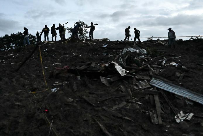 Reddingswerkers zoeken in de puinhopen na de aardverschuiving naar mogelijke slachtoffers.